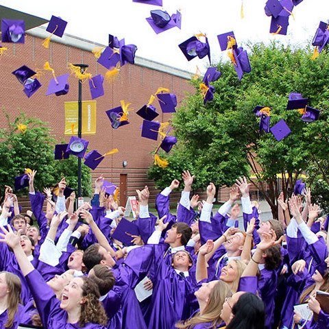 students in gowns throwing hats at graduation