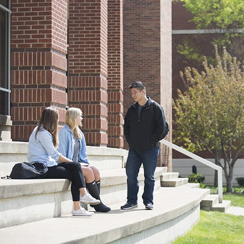 students sitting on campus building stairs