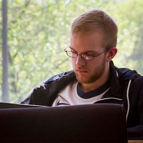 Student sits in common area working on laptop