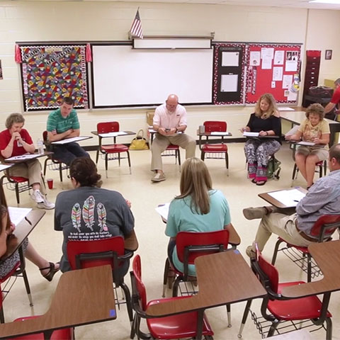 Teachers sit in desks in a circle during professional learning.