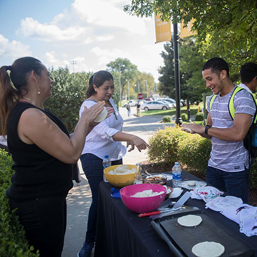 A student learns to make authentic tortillas during Fall Fiesta