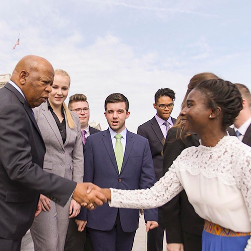 A student meets Rep. John Lewis on the steps of the U.S. Capitol