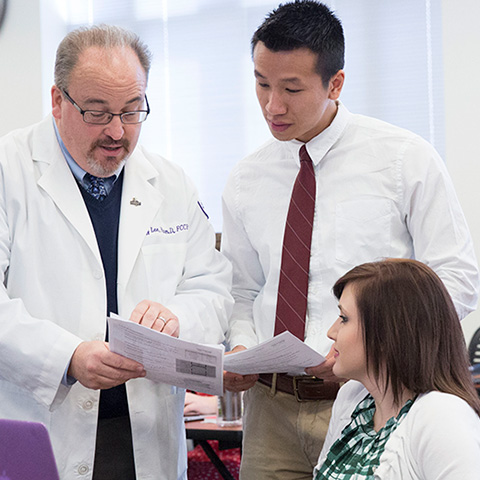 Pharmacy students work with a professor in class.