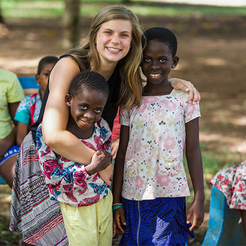 Student hugs children in Ghana during a mission trip