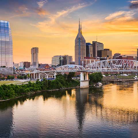 Nashville skyline at dusk with Cumberland river in the foreground.