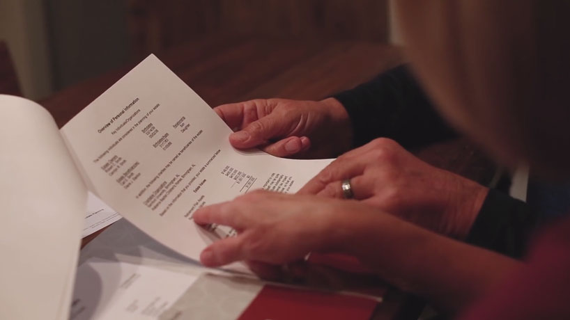 Hand of man and woman touching estate planning document