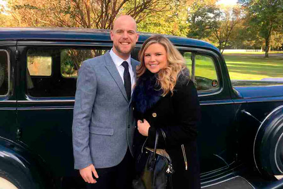 Ryan Bouch and his wife outside in front of antique black automobile.