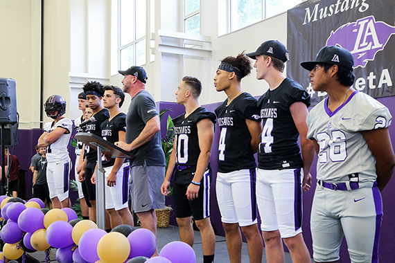 Seven football players and Coach Dilfer present the Lipscomb Academy Mustangs' new uniforms and helmet