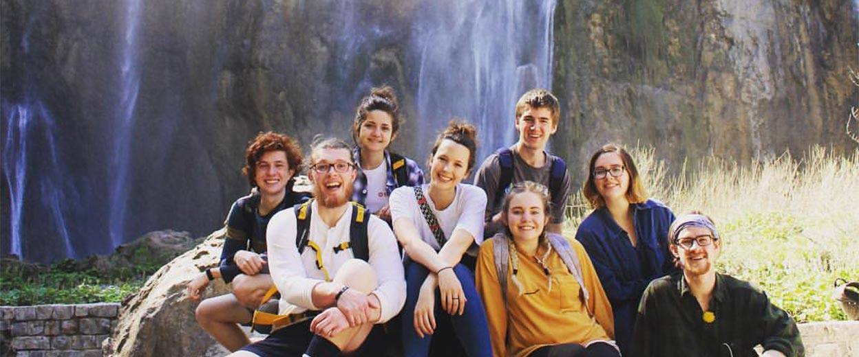 Students sit near a waterfall in the Alps