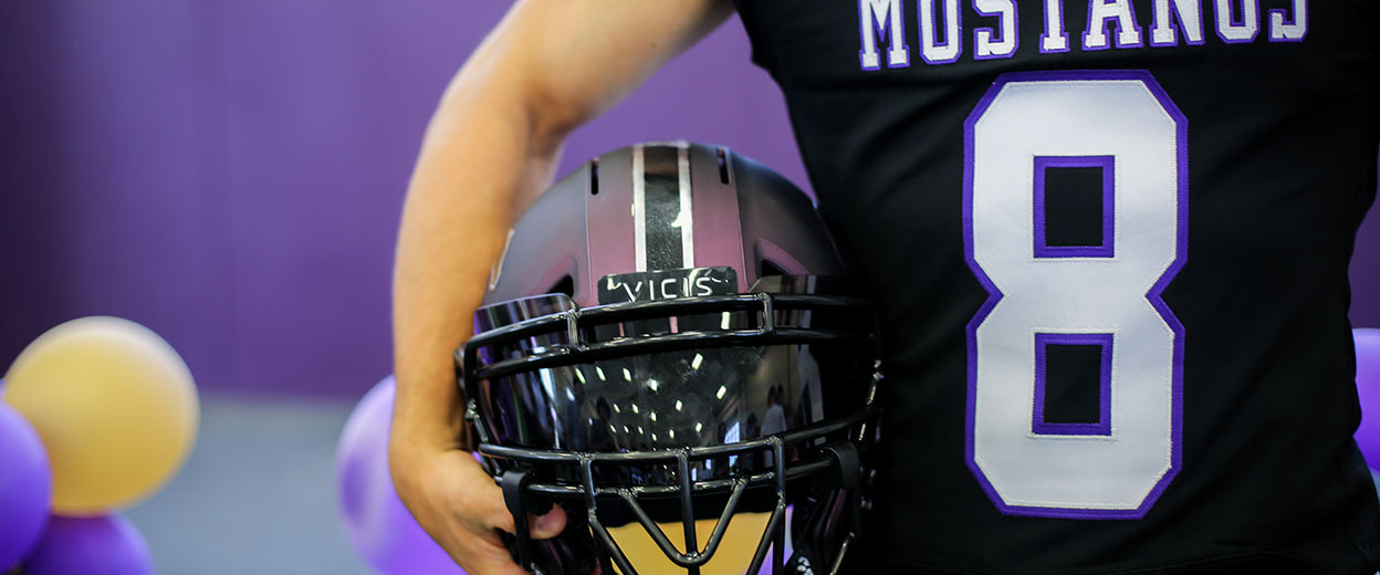 Moment from a football uniform reveal, football helmet being held by player with number 8 juersey
