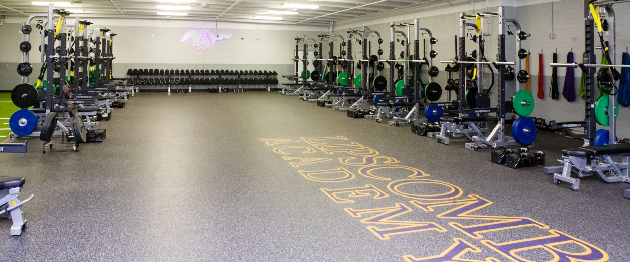 Weight room filled with two rows of weight racks