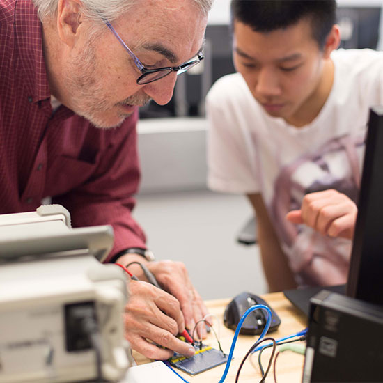 Engineering professor assists student with soldering during a electrical lab