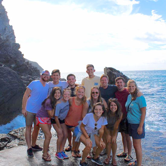 Study abroad students stand near the sea for a picture during an excursion.