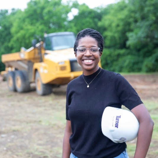 Michaela Kirk standing in front of a construction vehicle