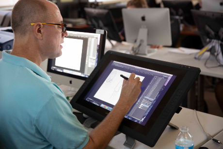 Tom Bancroft sits in a design studio at a tablet