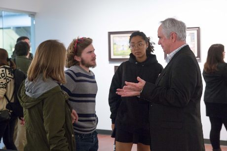 John Pomeroy talks with multiple students in a gallery