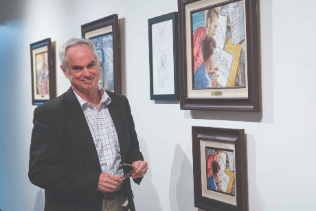 John Pomery stands in front of some his works at a gallery