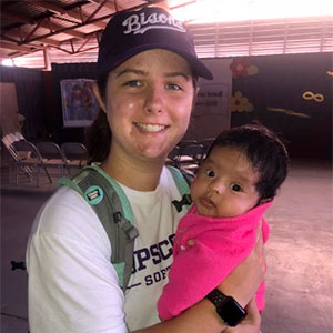 Softball student holds a infant on a mission trip to Baja, Mexico