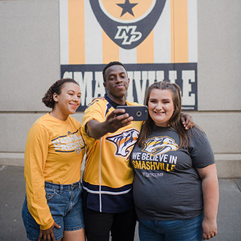 Three students take a selfie in front of the Smashville mural