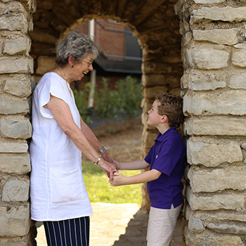An older woman and a young boy stand together holding hands, smiling in the archway