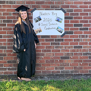 Noelle Lusk in cap and gown with a celebration sign