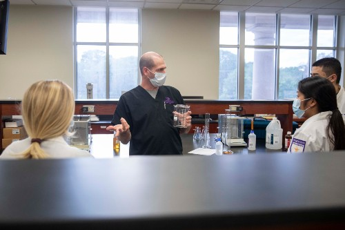DR. JIMMY TORR, ASSOCIATE PROFESSOR OF PHARMACY PRACTICE, GIVES INSTRUCTION ABOUT THE HAND SANITIZER COMPOUNDING PROCESS.