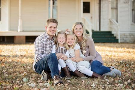 Brandon Lokey in a family portrait with his wife and two daughters.