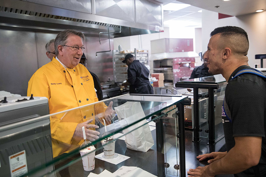 Lipscomb University President L. Randolph Lowry surprises students by serving them during the opening of Creekstone Burger Co.