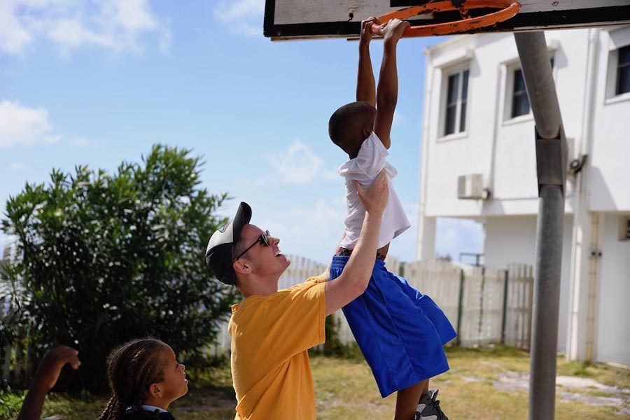 There are many opportunities for you to serve your community and world. Here, one of our students on mission in Saba gives a lift to a young friend during a game of basketball.