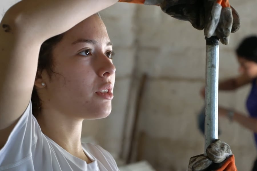 A female student examines a metal pipe