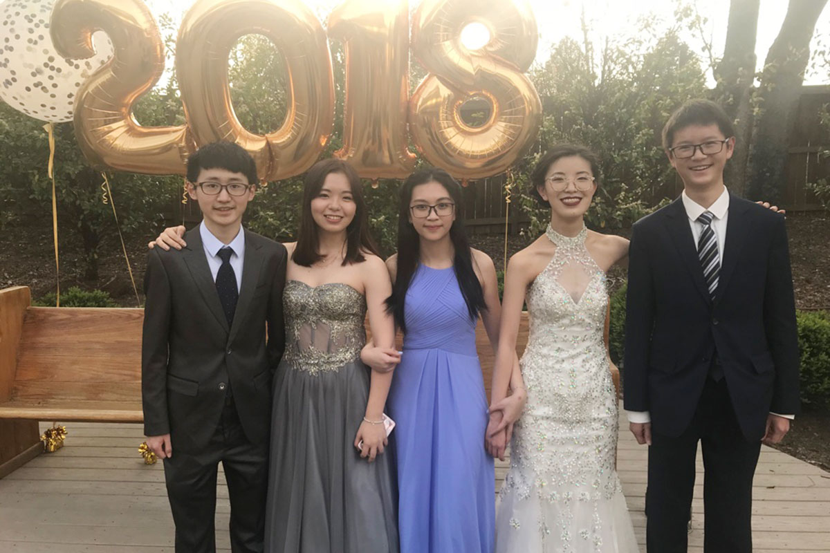 Global Students on a formal occasion with gold 2018 balloons in the background.