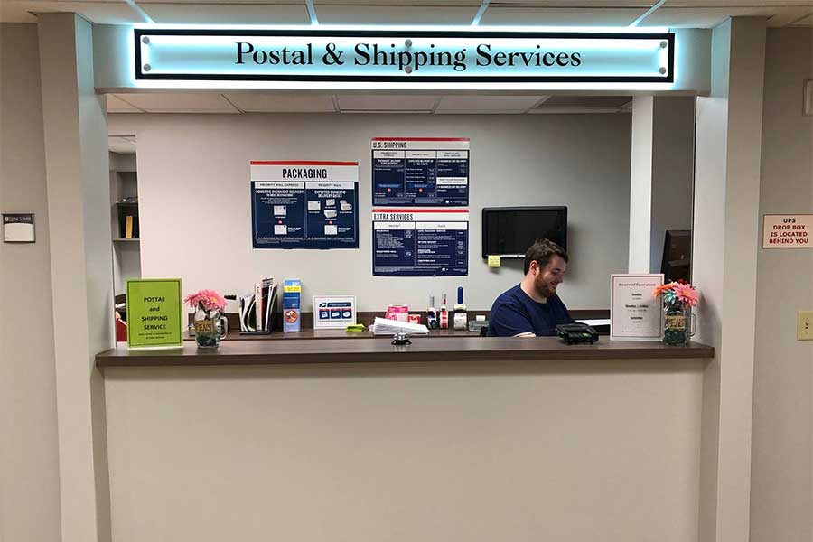 Shipping window at the Lipscomb Post Office with worker at counter.