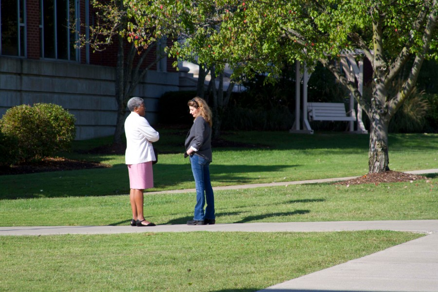 Norma Burgess standing outside on a sidewalk talking to a student on campus.