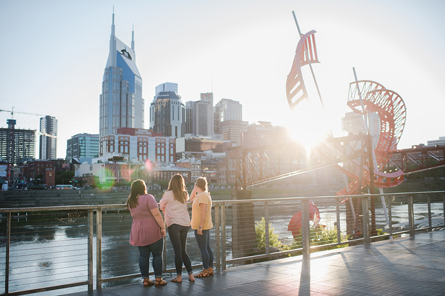 Students enjoy a walk at the park by Cumberland River and the Nashville skyline.