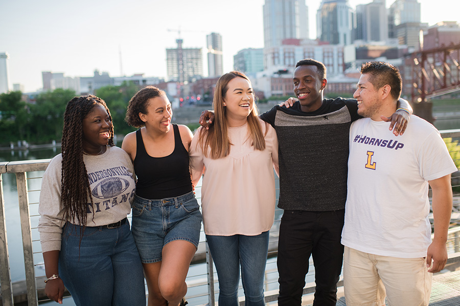 A diverse group of five Lipscomb students hanging out in Nashville in front of the skyline.