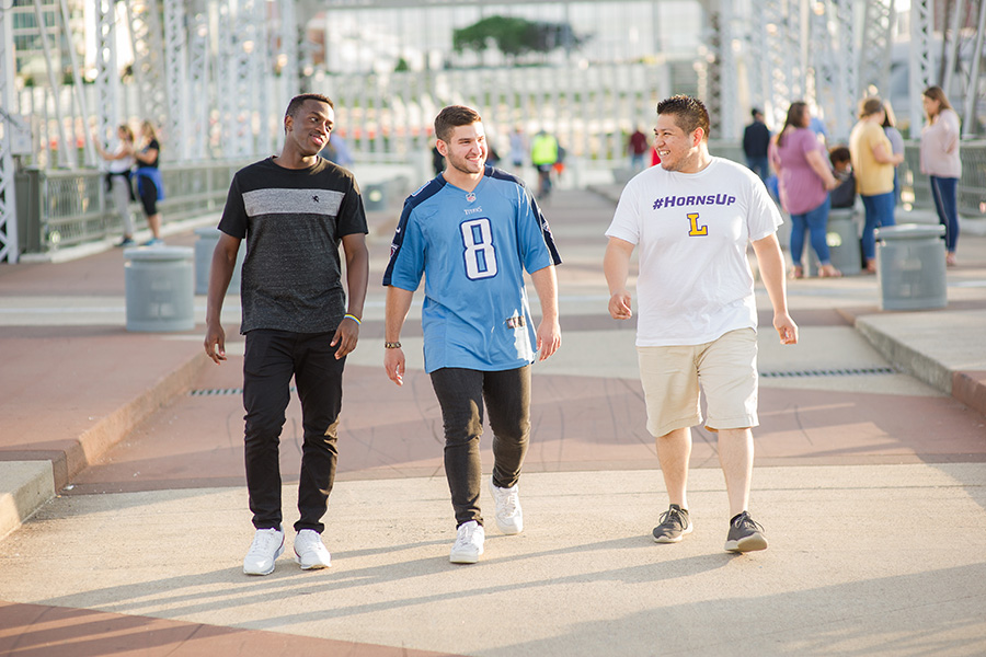 Three students walk together to a game in Nashville