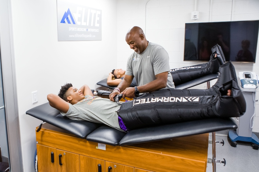 A physical therapist treats a student athlete