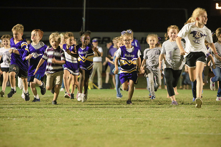 Young Mustang athletes run together across the football field at night