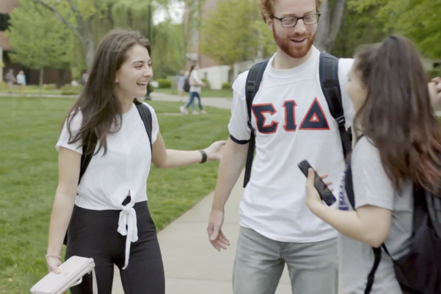 Students greet each other on the sidewalk