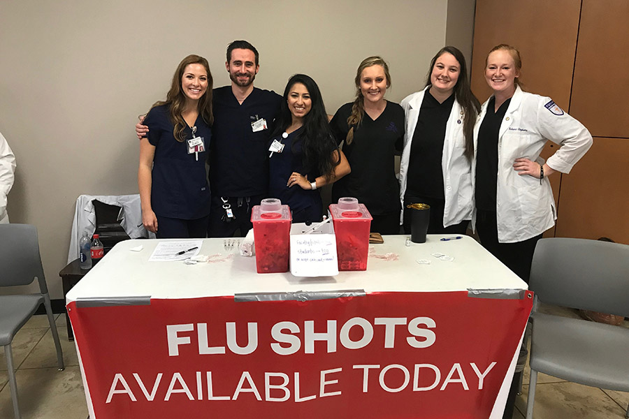 Student pharmacists gathered behind a flu shot booth with banner