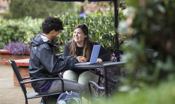 two students at outside table talking