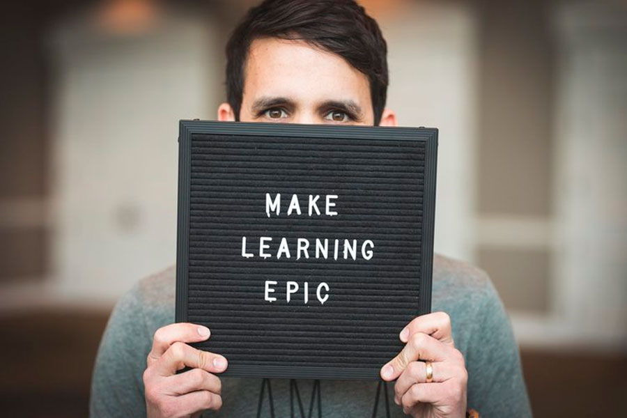 Trevor Muir holds sign saying: Make Learning Epic