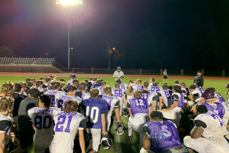 Football players taking a knee during a prayer.