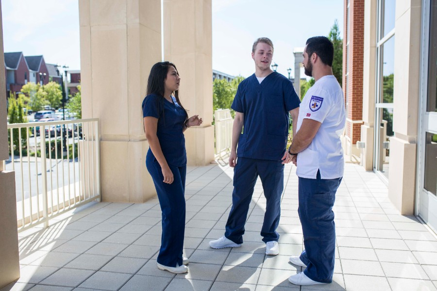 Two female and one male nursing students standing outside the Lipscomb nursing building.