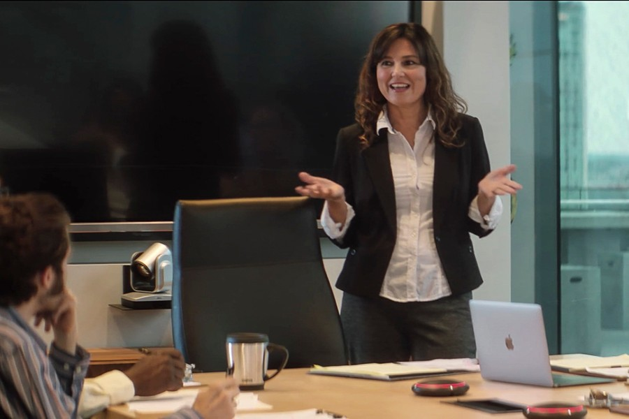 Woman in business setting standing and leading a discussion.