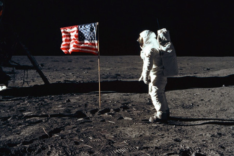 Neil Armstrong standing on moon near US flag.