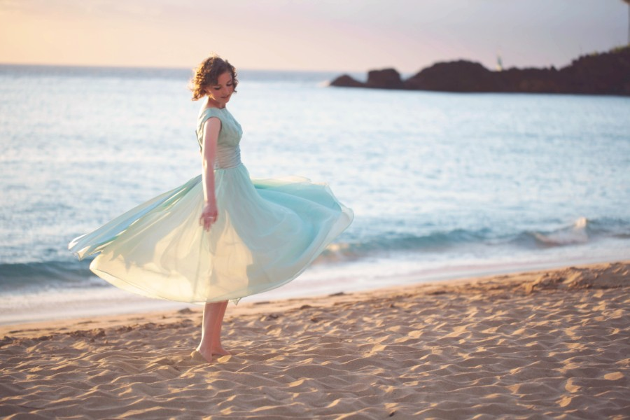 Emma Dryden twirling on a beach.