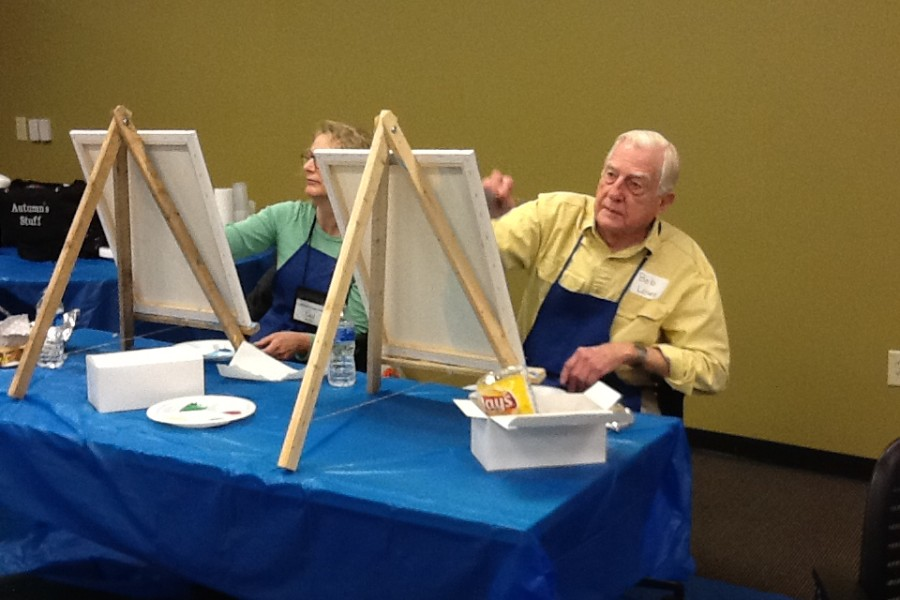 Older gentleman painting at an easel