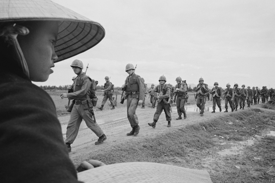 Photo from Vietnam War with soliders marching in a line in a field.
