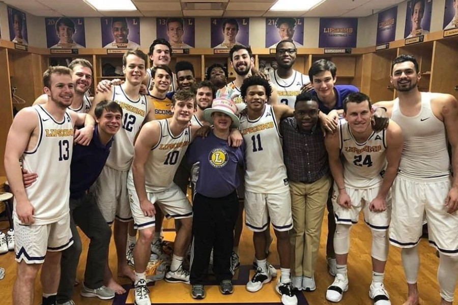Bison men's basketball team in lockerrroom standing with Conner.
